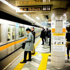 """Tokyo, Japan - February 20, 2012: People wait at a Tokyo Metro underground at 20:16 in the evening. Many are dressed in business attire and on their way home. A man can be seen checking his phone in the foreground. Image shot with an iPhone 4s and processed with instagram."""
