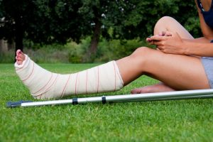 Leg in plaster of a girl sitting on the grass writing a text message with her smartphone. Crutches lying down at her side.