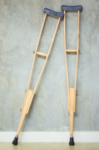 pair of old wooden crutches lean against the cement wall