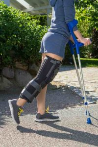 Young woman wearing an adjustable leg brace to support and immobilize her knee post operative, side view walking outdoors on crutches in a garden.